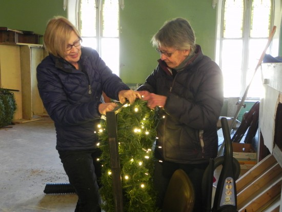 Meredith hanna and Maureen Ecclesine restring one of the 21 Holiday wreaths