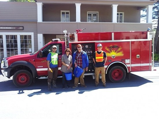 Dillon Klepetar, Barbara Kunzi, Ron Jackson, and Ben Breckenridge beside an Essex firetruck as they participate in the coin crop fundraiser.