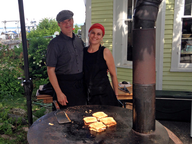 Russell Bailey & Kaska Barcz run Griddles, a wood-fired flat-iron kitchen on wheels. Seen here serving up grilled cheeses on Essex Day. (Source: Valley News)
