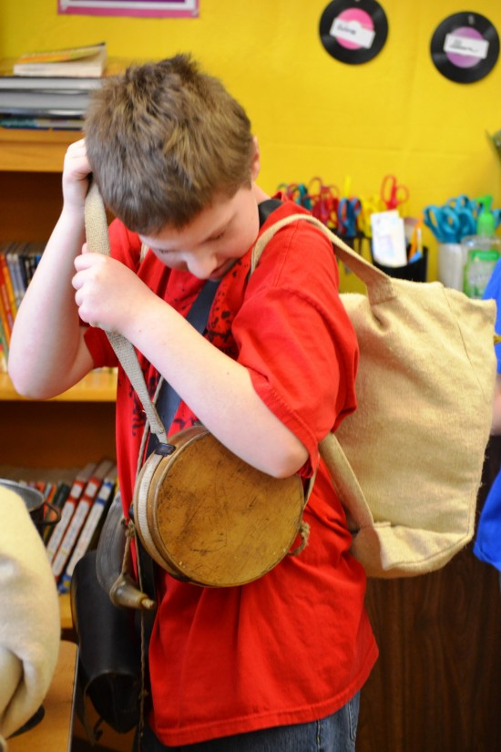 A student adjusts a canteen strap as he helps demonstrate the equipment worn by a soldier in the Continental Army in1775 during an outreach program led by staff from Fort Ticonderoga. Fort Ticonderoga has received grants to provide programs to fourth grade students in western Vermont and the Adirondacks at a greatly reduced cost to schools during the 2015-16 school year. (Credit: Fort Ticonderoga)