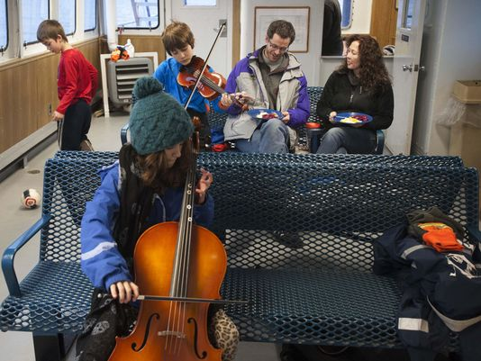 Ken Hughes and Susie Smith commute with their children Feb. 1, 2016, from Essex, N.Y., across Lake Champlain via ferry to Vermont. They finish breakfast in the passenger cabin while Oliver Hughes, 7, from left, plays with a ball, and Charlotte Hughes, 10, and Wyatt Trzaskos, 10, practice their music. (Photo: Glenn Russell, The Burlington (Vt.) Free Press)
