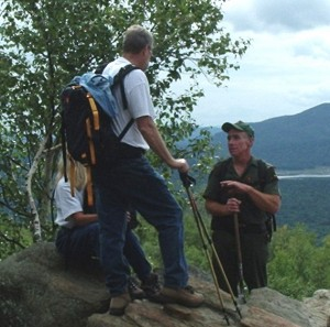 Photo: A Forest Ranger talks to backcountry visitors (DEC photo)