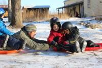 Gregg sledding with children at Lakeside