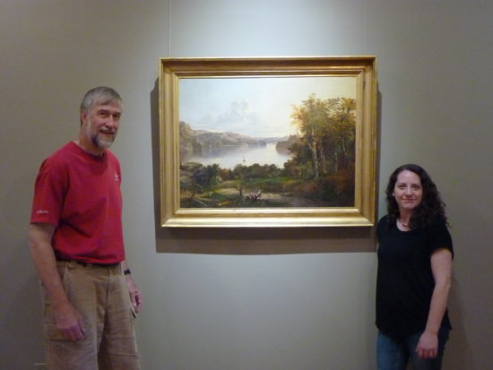 """Adirondack History Museum Board Member Steve Shepstone and Director Aurora McCaffrey pose in the new Rosenberg Gallery next to the Ambrose Andrews 1848 landscape of Fort Ticonderoga, the earliest landscape in the Museum's """"Hidden Treasures: Essex County's Artists"""" art show. The show, which is curated by SUNY Plattsburgh Art Department Chair Norman Taber, features notable works from the 19th Century, 20th Century and contemporary artists, and opens with a reception on Aug. 5. (Photo provided by the Adirondack History Museum)"""