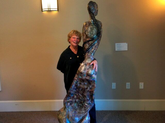 "Local sculptor Kate List poses in front of ""Hersea,"" a mixed media sculpture created, in part, from old issues of National Geographic. Part of a series, the statue is intended be moved to look like she's swimming. List displayed the sculpture, among others, at the Second Annual Sculpture Show at the Champlain Valley Senior Community, which concluded Sept. 9."