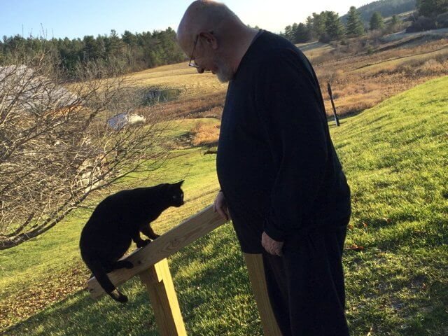 "Artist and theatre director Edward Cornell and one of his two black cats, Sasha, look across the Art Farm fields. Cornell will direct ""The Birds"" by Irish playwight Conor McPherson. (Photo by Kim Dedam)"