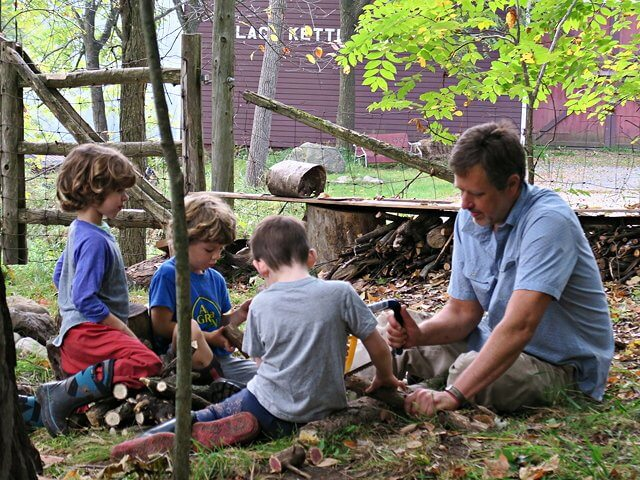 Kindergarten teacher Gregg VanDeusen gathers the kindergarten around the log pile on the lawn at Lakeside School. (Photo by Kim Dedam)