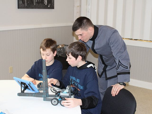 U.S. Military Academy Third Class Cadet and Ticonderoga graduate Brody Rocque works with Elizabethtown-Lewis student Ben Burdo and Willsboro student Kayden Reynolds during the STEM robotics program at CFES.( Photo by Keith Lobdell)