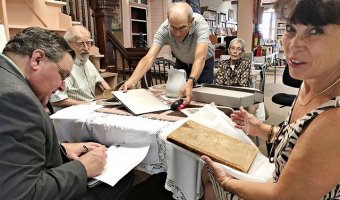 Pennsylvania State Archivist Jonathan Stayer signs paperwork to accept the antiquated minute-book from Essex homeowner Edie Morris, at right. Essex Town Councilman Jim LaForest, second from left, and his wife, Town Historian Shirley LaForest look on at the Belden Noble Library. Library Director Tom Mangano arranges the table, center. (Photo by Kim Dedam)